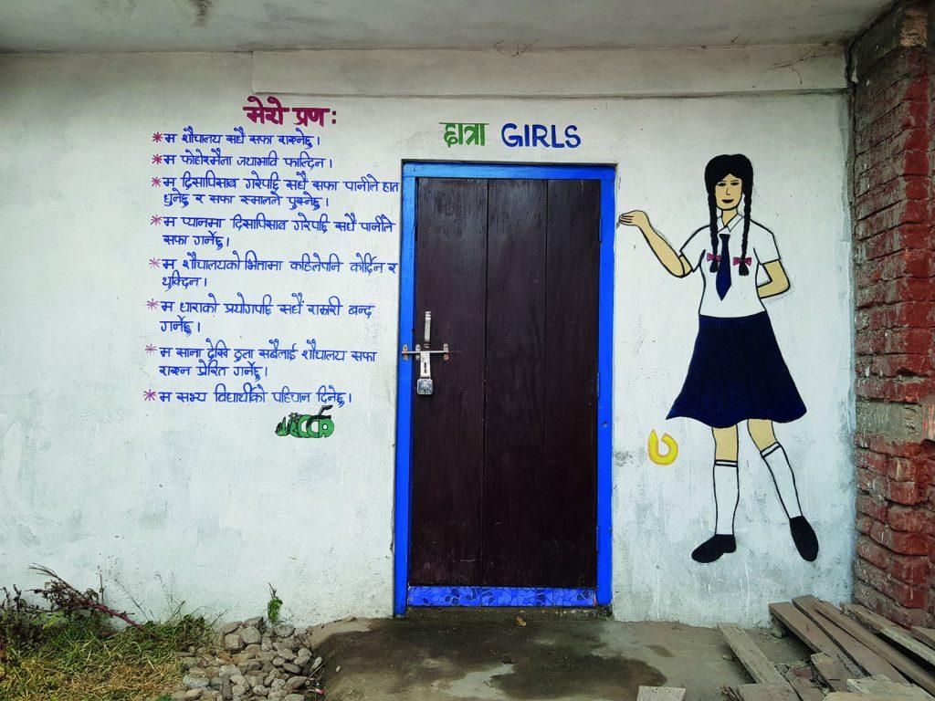 Seinämaalaus ja tekstiä tyttöjen vessarakennuksen seinässä nepalilaisessa koulussa.