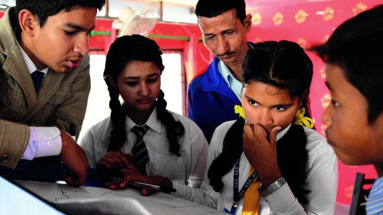 Nepalilaisia nuoria ja opettaja pohtimassa ryhmätyön ääressä.