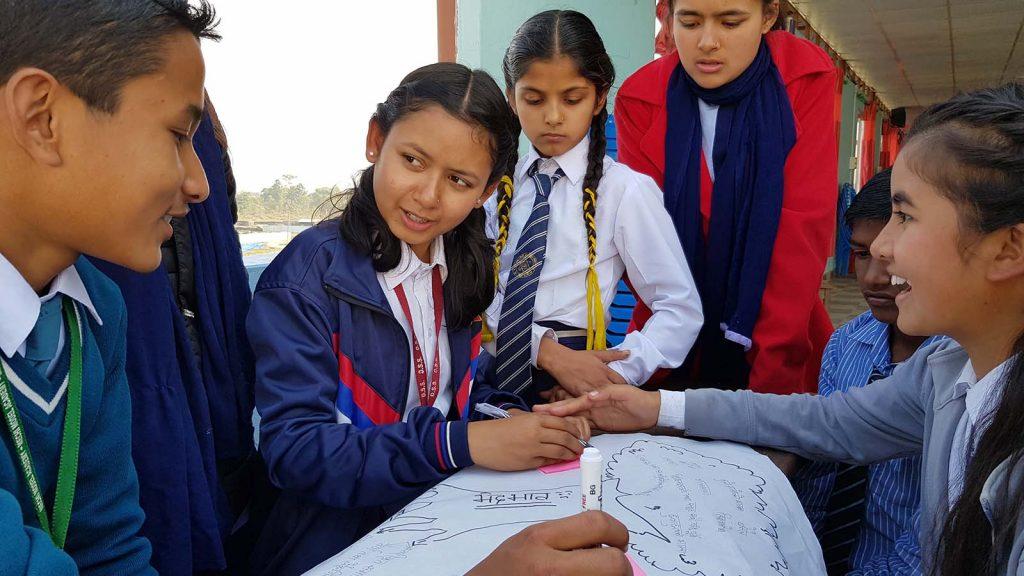 Pöydän ja ison julistepaperin ympärillä seitsemän nepalilaista nuorta keskustelemassa.