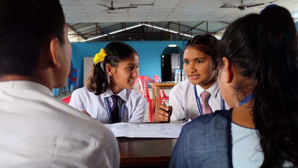Pöydän ympärillä neljä nepalilaista nuorta, joista yksi tyttö puhuu.