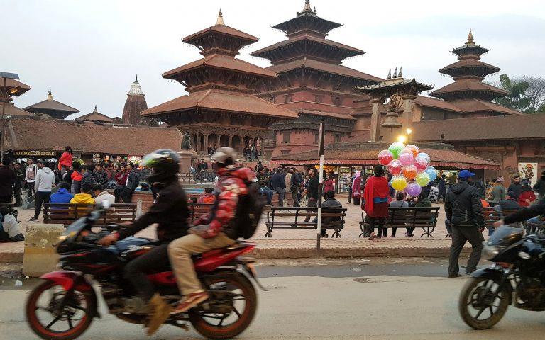 Katunäkymä Kathmandussa moottoripyörät ajavat ohi temppelialueen jolla on paljon ihmisiä.