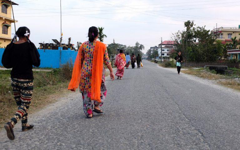 Katunäkymä Nepalissa naisia kävelemässä asvalttitiellä tien laidoilla matalia värikkäitä taloja.