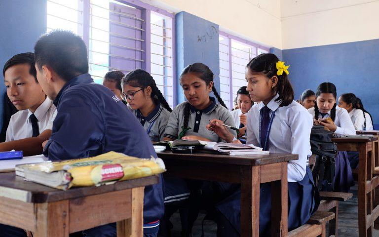 Koululuokka Nepalissa tyttöjä ja poikia koulupuvuissa istumassa pulpeteissa.