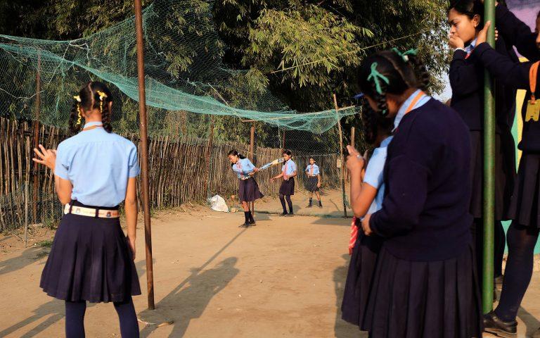 Koulupukuiset tytöt pelaavat krikettiä pihalla.