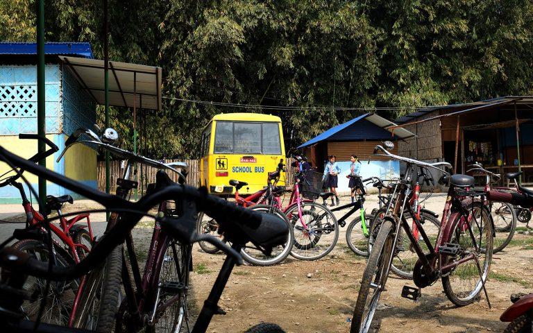Koulubussi ja kymmenen polkupyörää nepalilaisen koulun pihalla.
