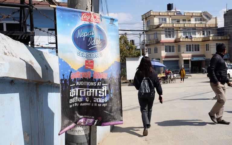 Katunäkymä Kathmandussa tyttö kävelee Idol-kisan mainoksen ohi.