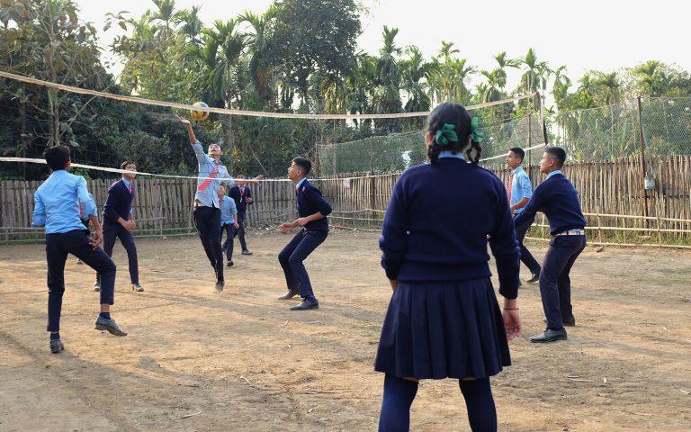 Kahdeksan poikaa ja yksi tyttö pelaavat lentopalloa pihalla.