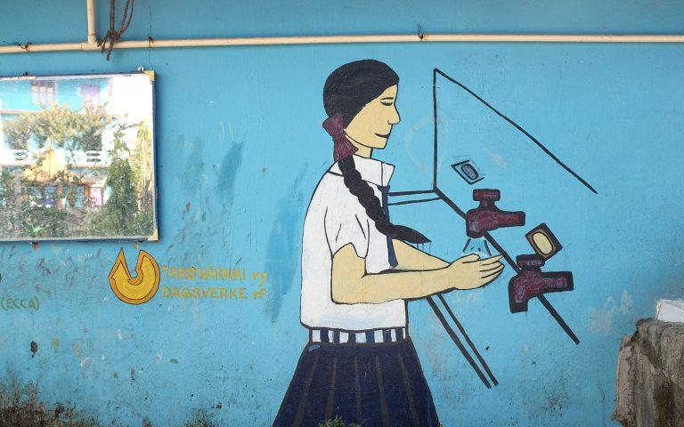 Seinämaalauksessa koulupukuinen tyttö pesee käsiään.