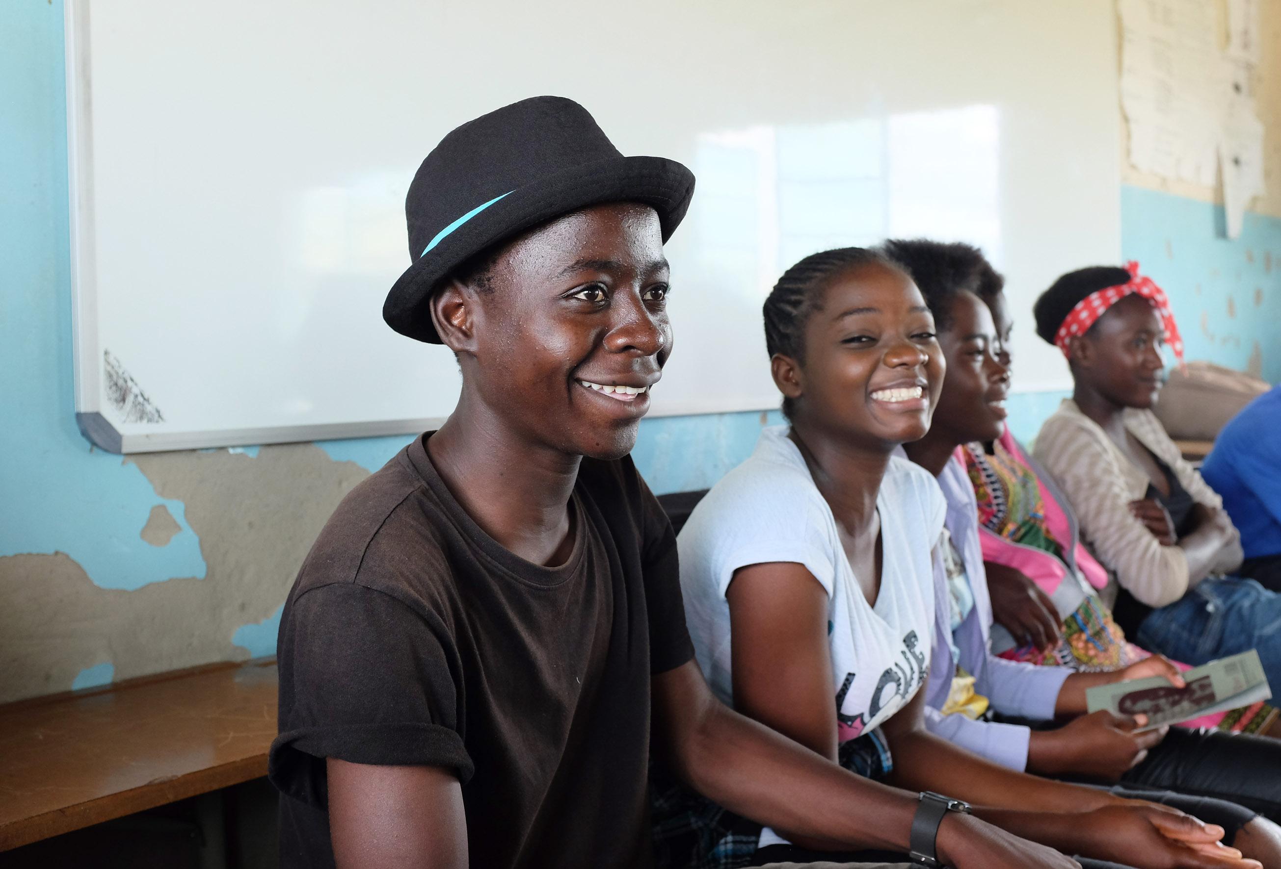 5 nuorta istuu luokassa penkillä.