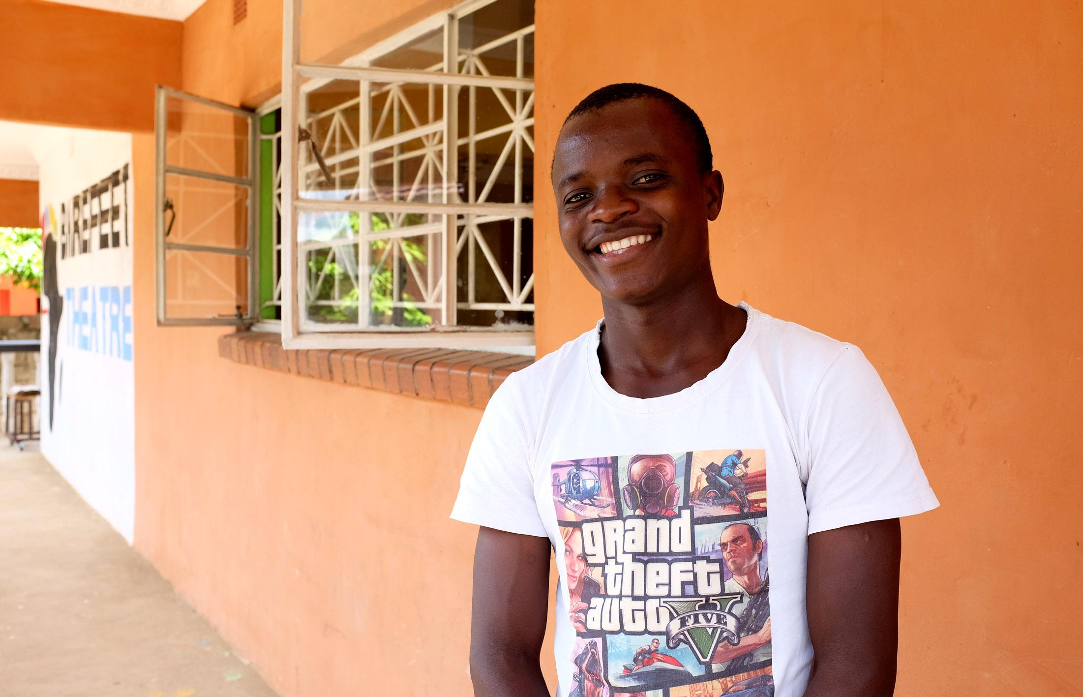 Hymyilevä nuori mies seisoo ulkona seinän edessä.