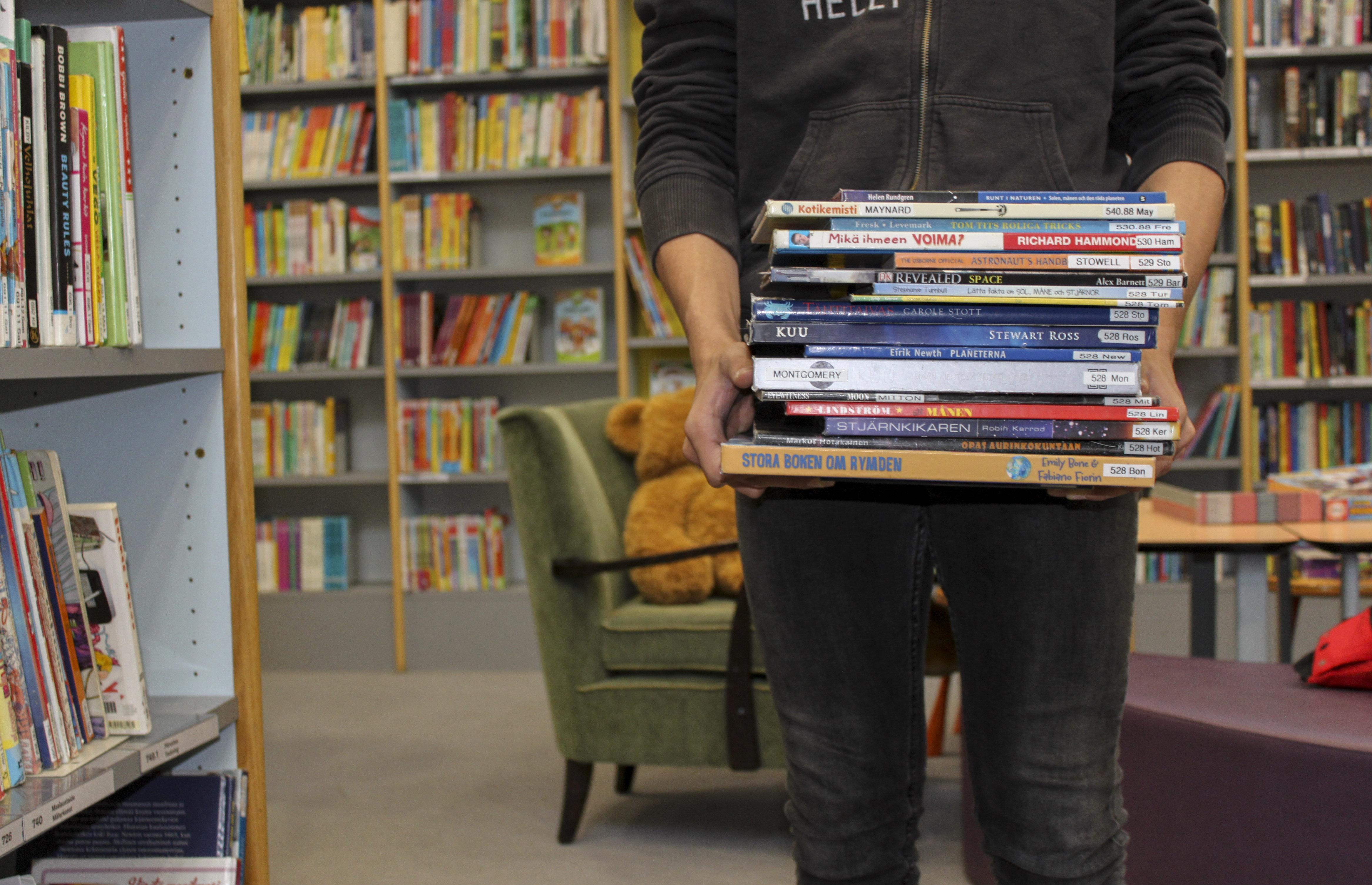 Poika kantaa kirjapinoa.