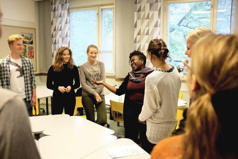 Opiskelijoita ja ohjaaja koululuokassa.