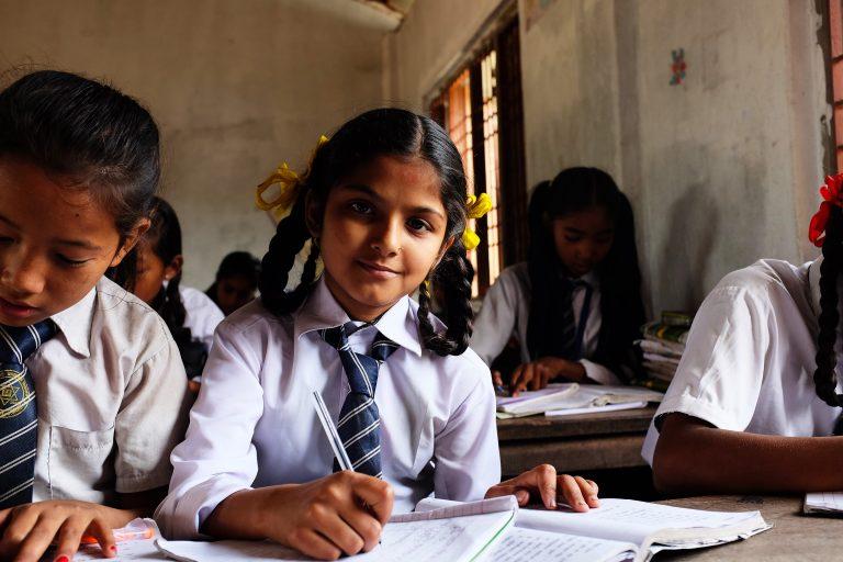 Tyttö istuu pulpetissa koululuokassa.