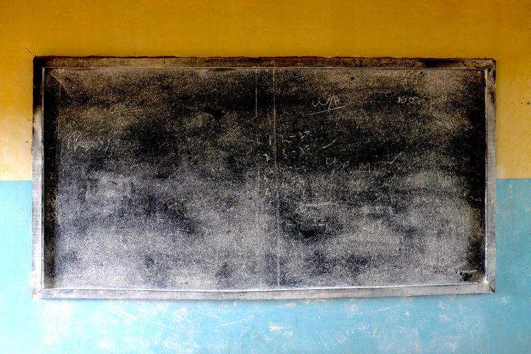 Musta liitutaulu keltasinisellä seinällä.