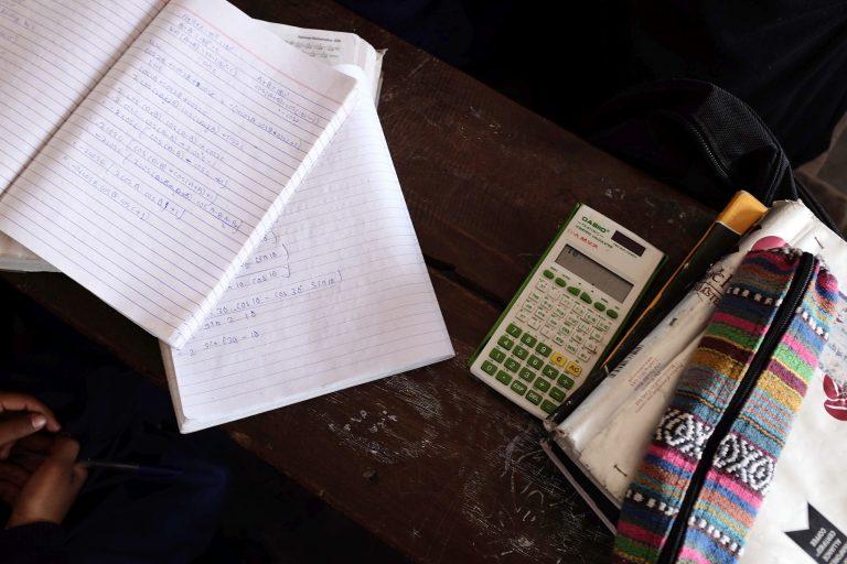 Kouluvihkoja, penaali ja taskulaskin pulpetilla.