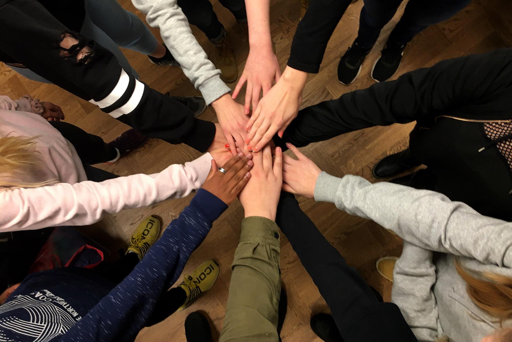 Ringissä seisovien nuorten kädet yhteen ojennettuina.