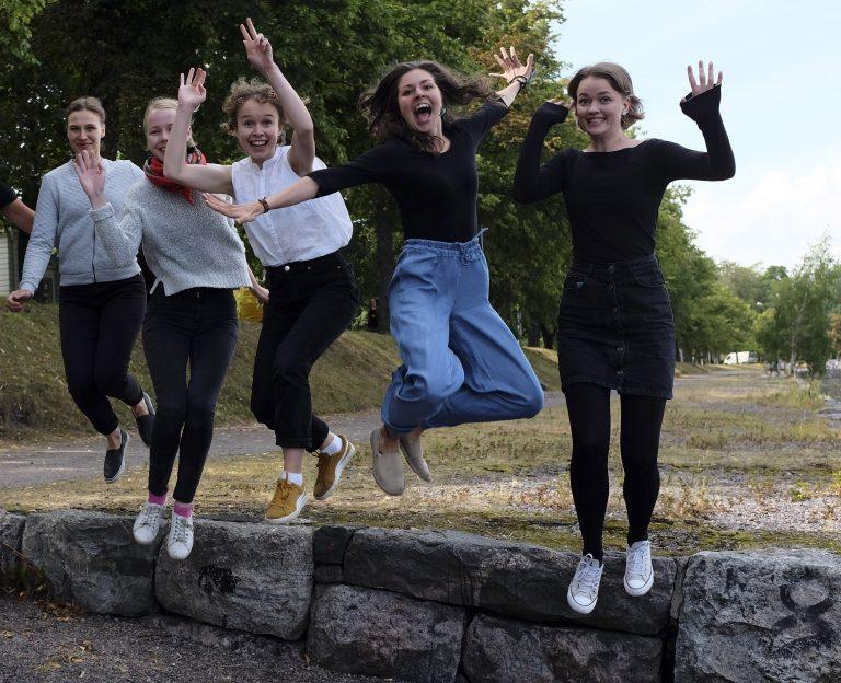 Viisi henkilöä hyppää ilmaan ryhmäkuvassa.