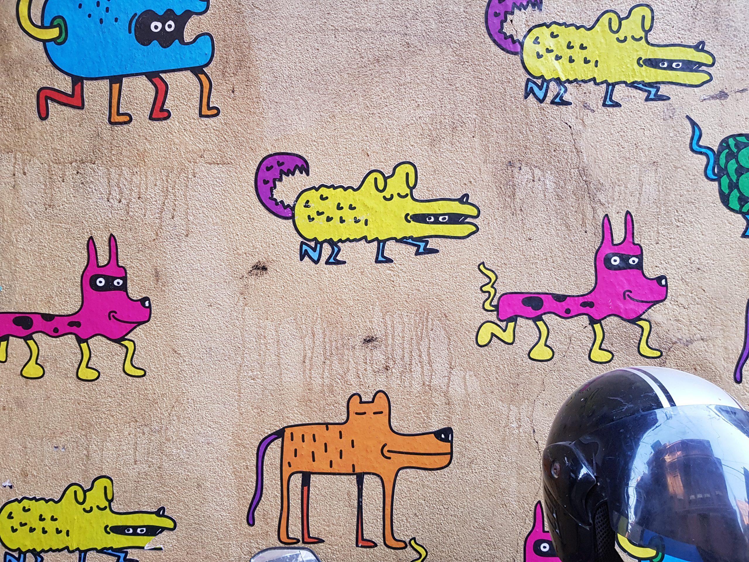 Seinämaalauksessa pieniä koiria.
