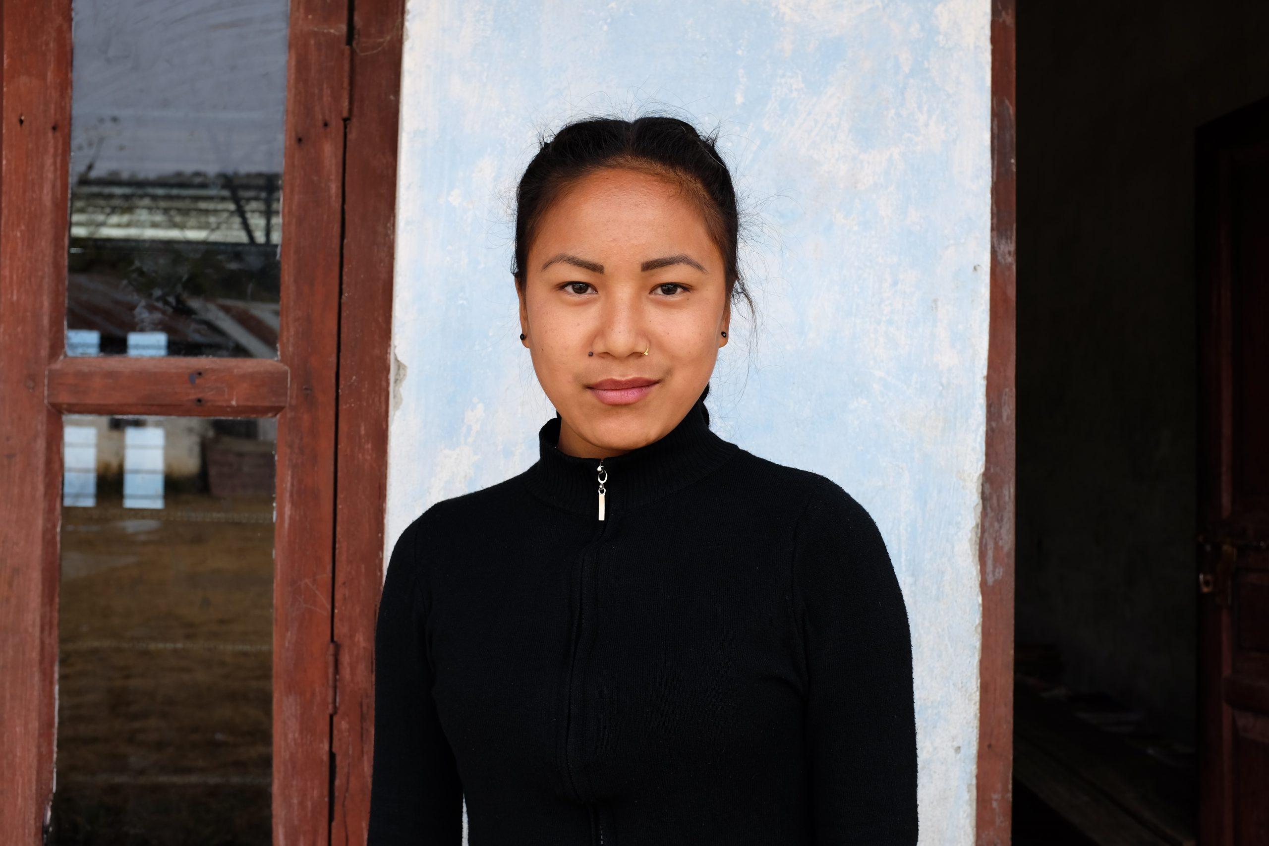 Nepalilainen tyttö koulun seinän edessä.