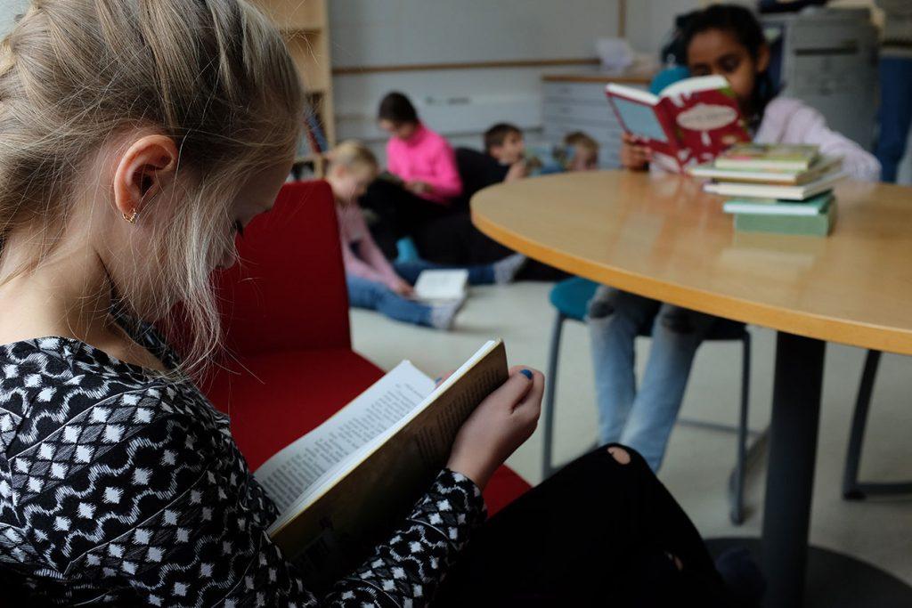 Lapsia koulun tiloissa lukemassa kirjoja.