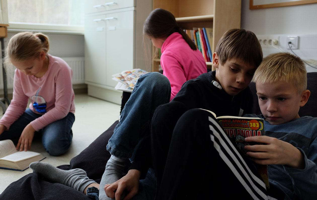 Neljä lasta lukemassa kirjoja.