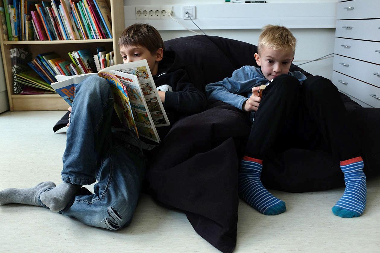 Kaksi poikaa istuu lattialla lukemassa sarjakuvia.