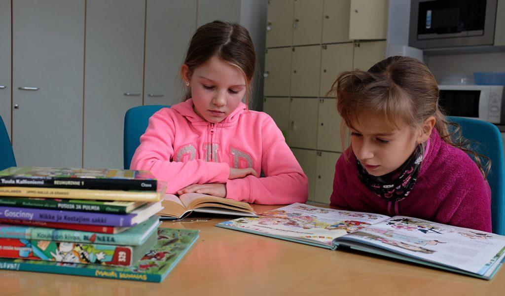 Kaksi tyttöä lukemassa kirjoja pöydän ääressä.