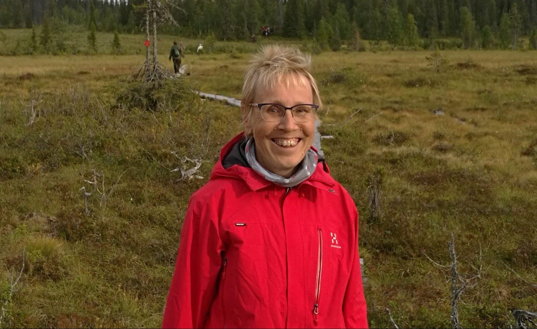 Nainen seisoo luonnossa ja hymyilee.