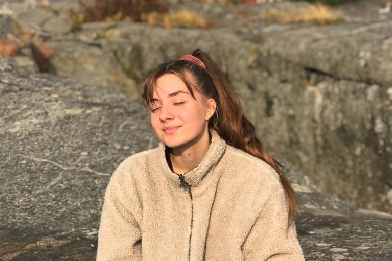 Henkilö istuu kalliolla.