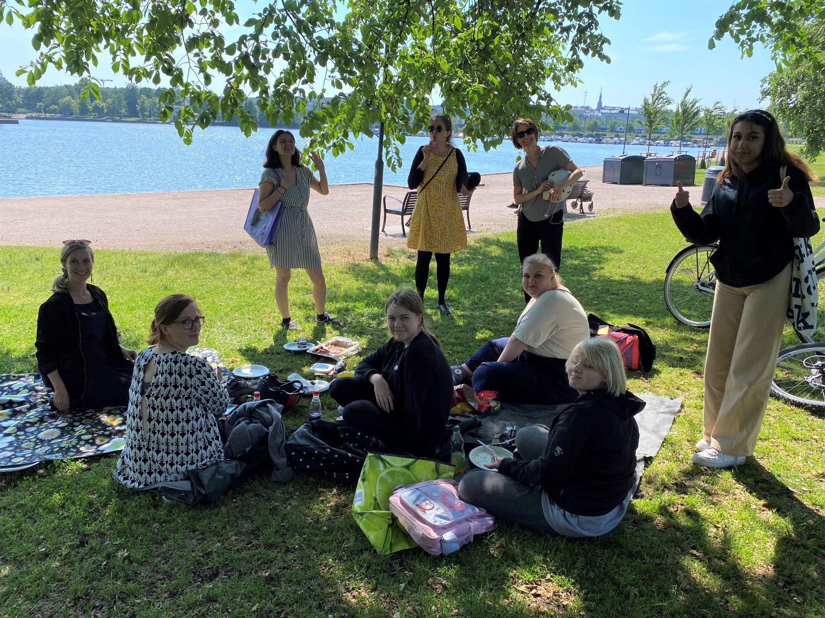 Ryhmä työntekijöitä ja nuoria piknikillä puistossa.