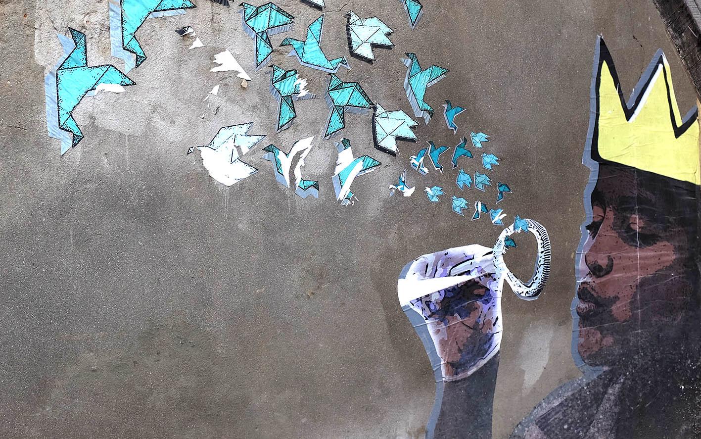 Seinämaalauksessa lapsi puhaltaa origamilintujen muotoisia saippuakuplia.