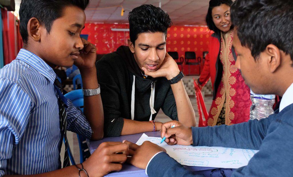 Neljä nepalilaista nuorta pöydässä ryhmätyön äärellä, Taksvärkki kampanjan kuvitusta.