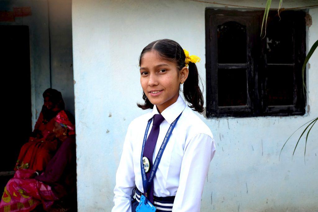 Nepalilainen tyttö koulupuvussa seisoo talon ulkopuolella.