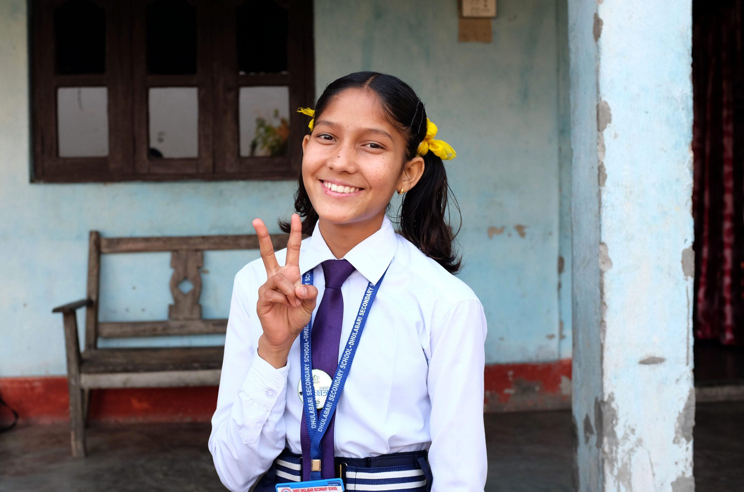 Tyttö koulupuvussa katsoo kameraan ja hymyilee.