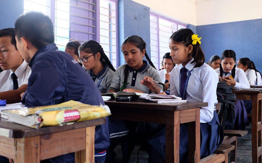 Luokkahuone Nepalissa pulpeteissa istuu koulupukuisia tyttöjä ja poikia.
