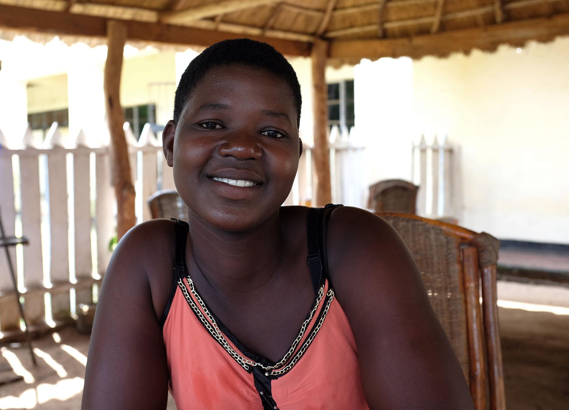 Hymyilevä malawilainen nuori nainen istumassa ulkona varjossa.