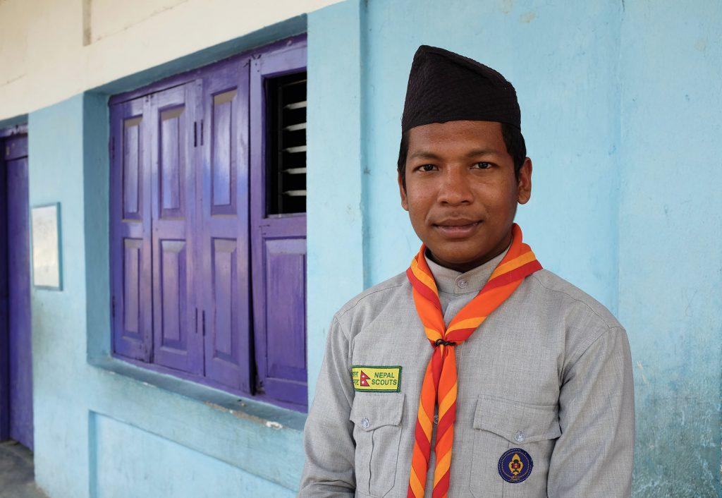 Nepalilainen poika seisoo ulkona seinän edessä ja katsoo kameraan.