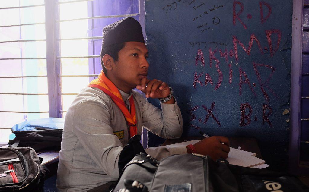Nepalilainen poika istuu pulpetissa koululuokassa.