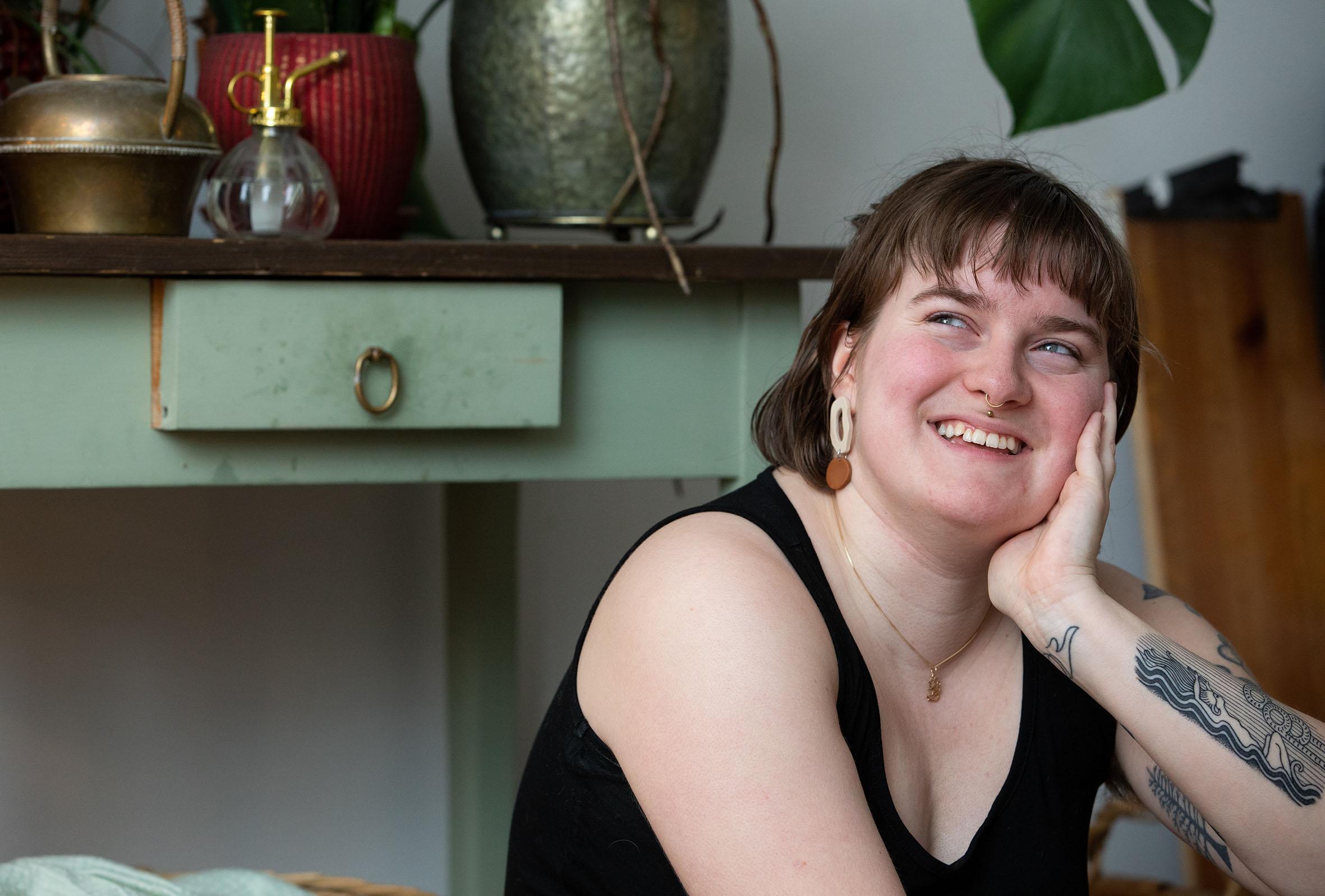 Hymyilevä Julianna Brandt istuu ja nojaa kämmeneensä, taustalla värikkäitä kukkaruukkuja pöydällä.