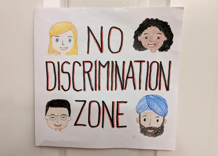 Paperille on piirretty 4 erilaisen ihmisen kasvot, keskellä on teksti No discrimination zone eli Syrjinnästä vapaa alue.