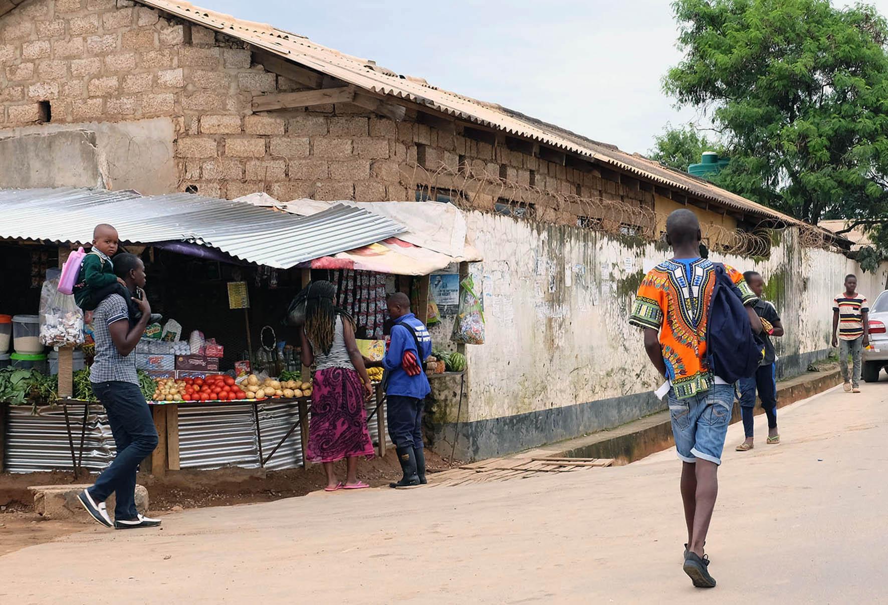 Rauhallinen asvalttipäällysteinen katu Lusakassa Sambiassa, nuori kävelee kadulla reppu selässään, vastaan kävelee 2 nuorta. Kadun laidassa on ruoka- ja vihanneskioski., jonka edessä on 3 aikuista ja yksi pikkulapsi.