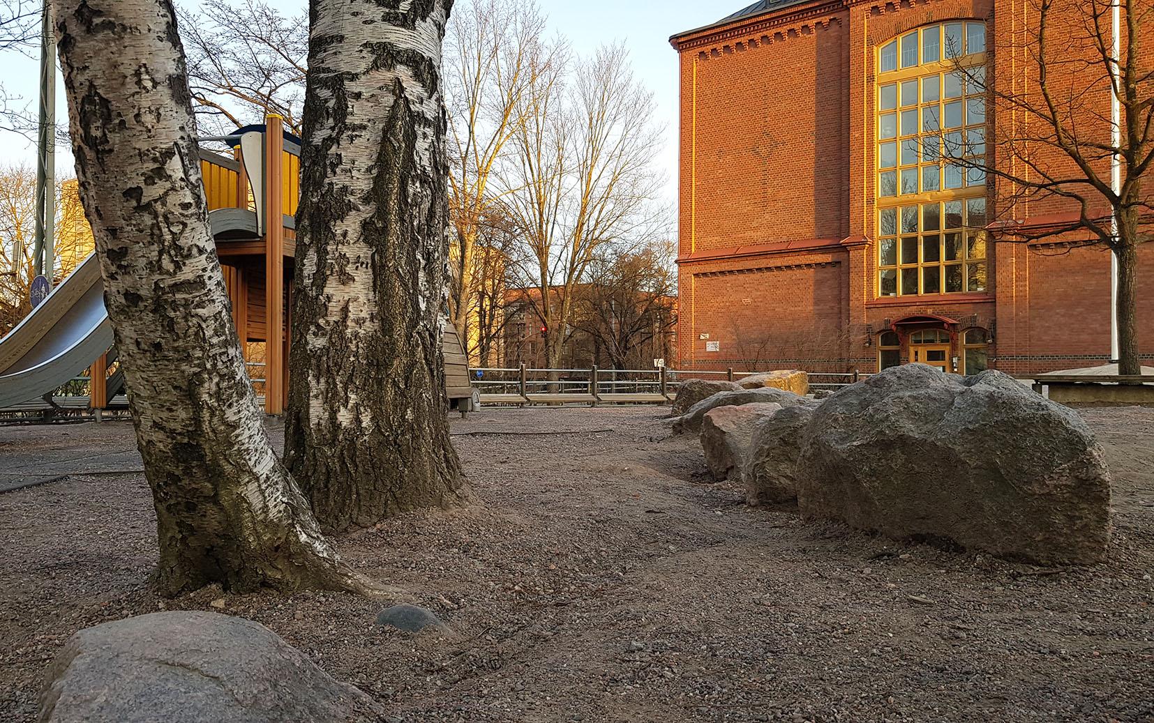 Koulun pihalla hiekkakenttää, 7 suurta kiveä, 2 koivunrunkoa ja liukumäki, taustalla punatiilinen vanha koulurakennus.