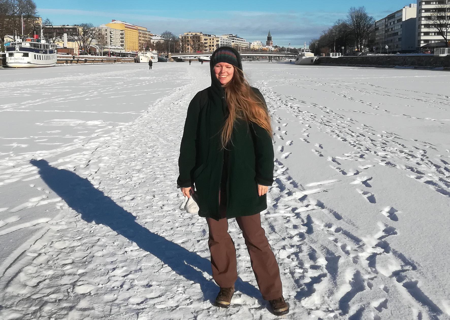Pitkähiuksinen nuori nainen talvivaatteissa seisoo lumessa joen jäällä kaupungin keskustassa.