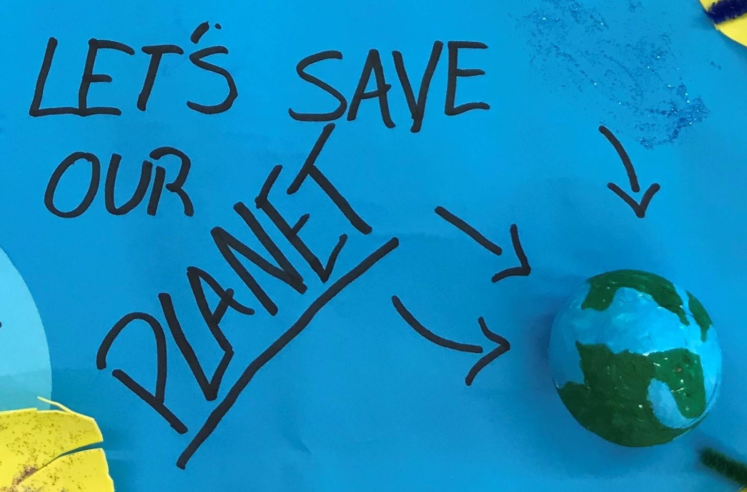 Yksityiskohta askartelukollaasista, jossa sinisellä pahvipohjalla on pieni maapalloksi maalattu pallo ja mustalla tussilla englanniksi teksti Let's save our planet eli Pelastetaan planeettamme.