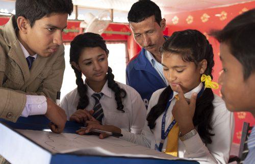 Neljä oppilasta ja opettaja seisovat pöydän äärellä.