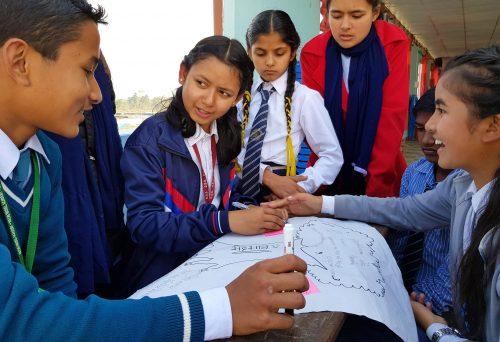 Oppilaskunnan jäseniä pöydän ääressä Nepalissa.