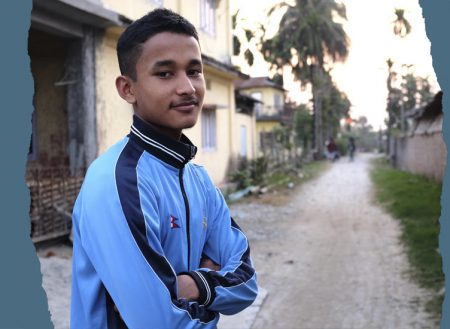 Nepalilainen poika seisoo ulkona ja katsoo kameraan.